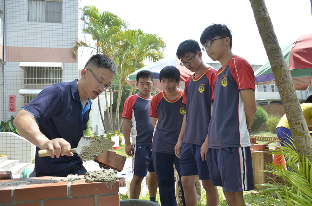 砌磚國手周承誼(左一)指導學生磚塊疊砌。
