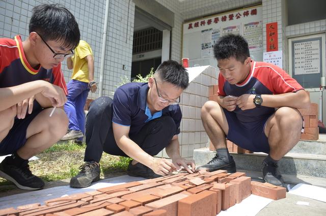 砌磚國手周承誼(中)指導學生試排磚塊。