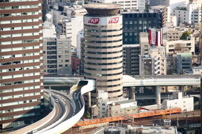 位於大阪阪神高速公路梅田出口附近的一棟圓形建築物,剛好被高速公路正面穿過,形成大阪街景中的一幅奇特畫面。這棟大樓名稱叫「門塔大廈」(TKP Gate Tower Building),是由出租會議室的大型業者TKP所管理的地上16層建築物,內有34間會議室。